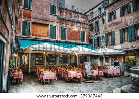 restaurant tables and chairs in a small square in Venice, Italy