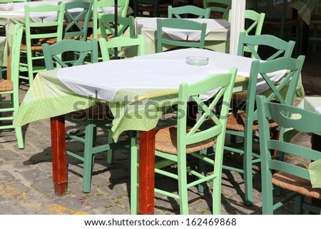 Restaurant tables and green chairs in Athens, Greece