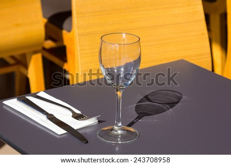 restaurant tables with silverware and glasses ready for a lunch or dinner - stock photo