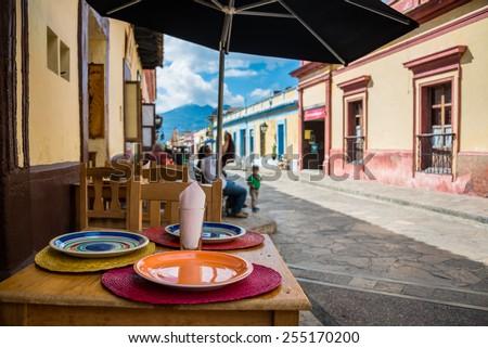 Restaurant view and sidewalk on San Cristobal de las Casas colonial town. Latin American Culture. - stock photo