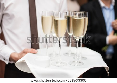 Restaurant waiter brings people and alcohol champagne on a tray - stock photo