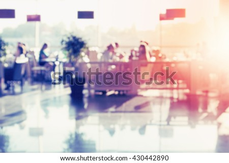 Restaurant with big windows. Many people eating. Blurred image.