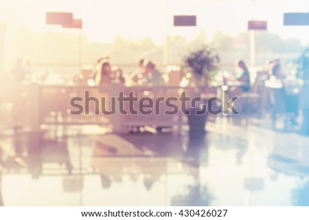 Restaurant with many people eating. Pastel colors. Blurred image.