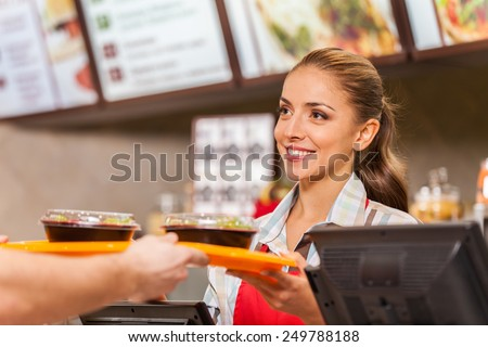 Restaurant worker serving two fast food meals with smile. woman holding tray with salads at fast food restaurant - stock photo