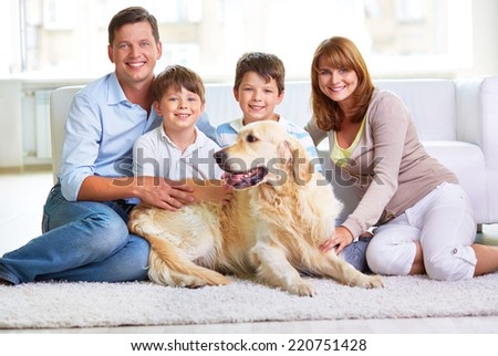 Restful family members and Labrador sitting by sofa