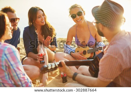 Restful friends with drinks and guitar spending leisure on sandy beach - stock photo