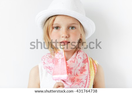 Restful little European girl with yummy popsicle posing for camera. In summer hat and nice scarf she looks like traveller enjoying her happy child life and sweets. - stock photo