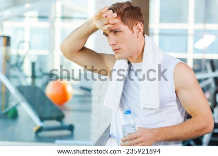 Resting after work out. Tired young man carrying towel on shoulders and touching his forehead while standing in gym - stock photo