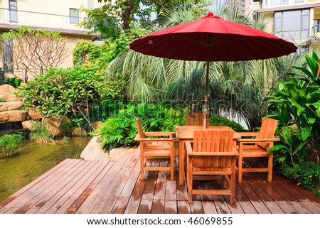 Resting area with tables and wooden chairs under umbrella in garden
