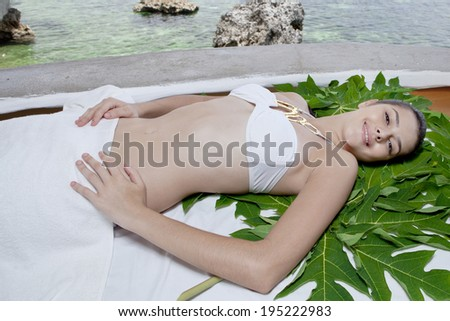 resting Asian woman on palm leaves in Boracay in Philippines