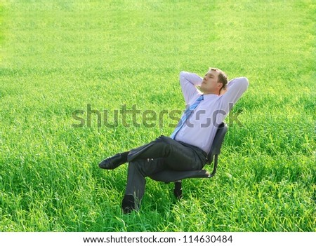 Resting businessman relaxing on a chair on a green meadow - stock photo