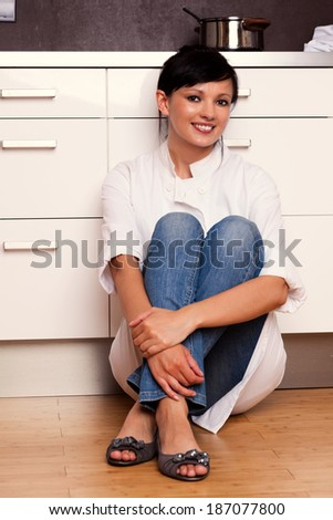 resting cook, beautiful young woman sitting on the kitchen floor - stock photo