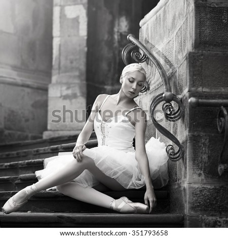 Resting grace. Monochrome soft focus portrait of a sensual young ballerina sitting on stairs