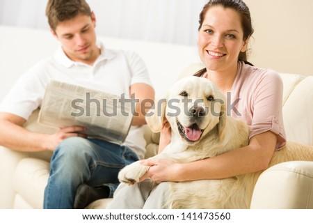 Resting joyful couple sitting and petting dog man reading newspaper - stock photo