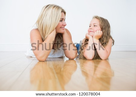 Resting mother and daughter on the floor while they looking at each other - stock photo