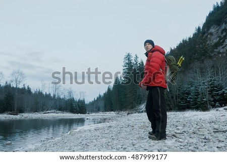 Resting mountaineer with alpinist backpack and equipment standing on pebble river bank at winter evening rocky landscape background