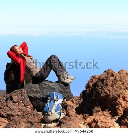 Resting relaxing woman hiker lying down enjoying the sun during hiking travel trek on volcano Teide, Tenerife, Canary Islands, Spain. Beautiful young female hiker. - stock photo