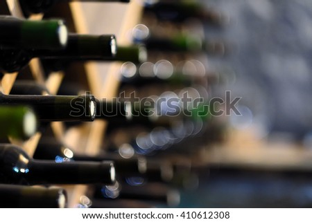 Resting wine bottles stacked on wooden racks in cellar  - stock photo