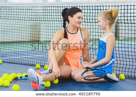Resting young woman or tennis coach with girl sitting near net - stock photo