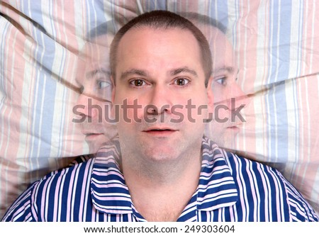restless man lying in bed - stock photo