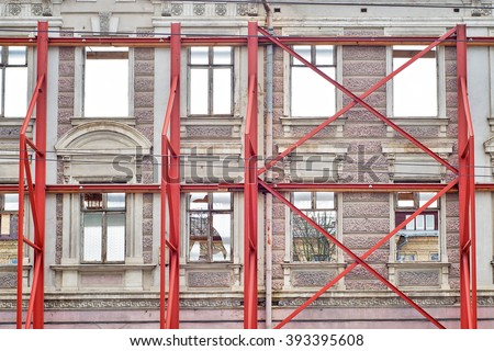 restoration facade of old house, red steel structure forms to avoid collapsing - stock photo