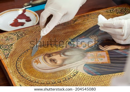 restoration of old gilded icon with  filling knife at workshop - stock photo