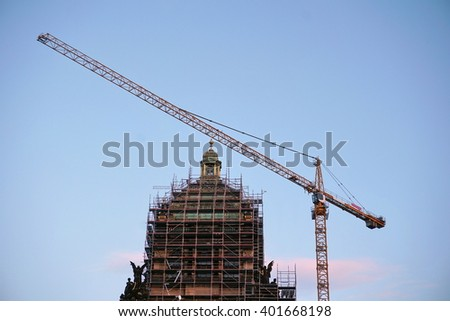 Restoration of the historical building of the National Museum in Prague, with a tall crane and silver metal scaffolding  - stock photo