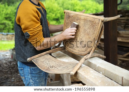 Restoration, removing paint from antique chair with sandpaper - stock photo