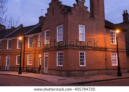 Restored Edwardian brick houses on a local road at night with street lamps - stock photo