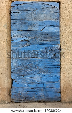 Restored narrow door of a small ancient passageway into a garden. France, Provence - stock photo