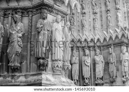 restored statues in contrast with the old ones, on the front of Cathedral of Notre-Dame, Reims, France (Black and white) - stock photo