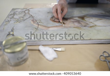 Restorer working old painting restoration. - stock photo