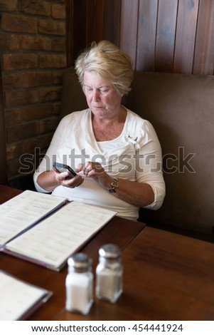 Restrained senior woman sitting in a restaurant reading messages on her smartphone - stock photo