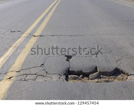 Restricted local government budgets are reflected in potholes and damaged roads - stock photo