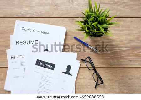 Resume applications on wooden desk ready to be reviewed