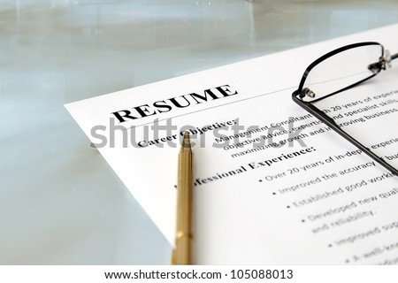 Resume on the Table. Closeup of resume with pen and glasses on the table