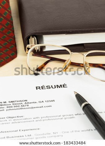 Resume, pen, neck tie, glasses, and notebook - stock photo