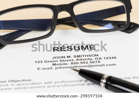 Resume with pen and glasses; resume is mock-up - stock photo