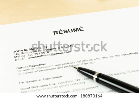 Resume with pen on table closeup - stock photo
