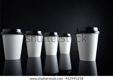 Retail mockup presentation, Luxury set of white take away cardboard paper cups closed with caps isolated on black and mirrored. One cup presented in front - stock photo