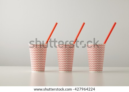 Retail set of three paper cups decorated with red line pattern and with red drinking straw inside isolated on white table Place for your text above - stock photo