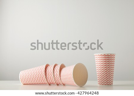 Retail set of three paper cups decorated with red lines pattern felt down and one standing near isolated on white table - stock photo