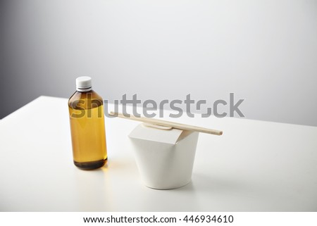 Retail takeaway commercial set: plastic brown bottle with tasty beverage on left side of closed blank wok box with wok noodles inside and chopsticks on top isolated on white - stock photo