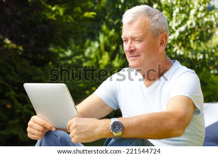 Retired casual man sitting with digital tablet at home in garden.  - stock photo