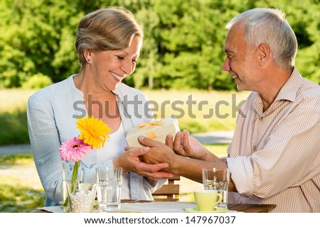 Retired Caucasian couple smiling and  holding gift outdoors