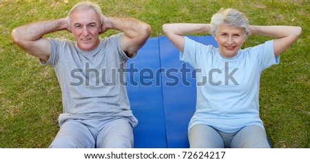 Retired couple doing their streches in the garden - stock photo