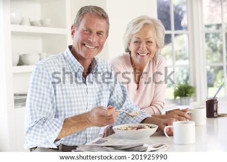 Retired couple eating breakfast - stock photo