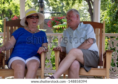 Retired couple having fun conversations. Woman is laughing while her husband happily looking at her - stock photo