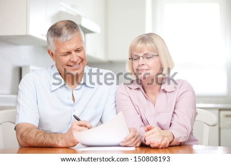 Retired couple signing documents
