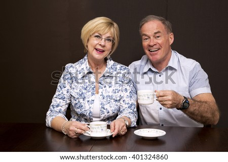 retired couple sitting by the table having coffee dark background - stock photo